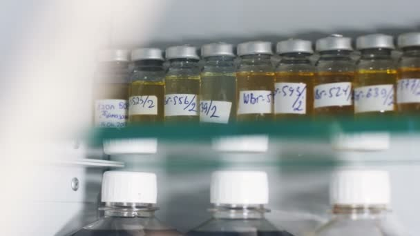 Closeup small bottles with yellow and black oil product samples on shelf in lab case with glass door