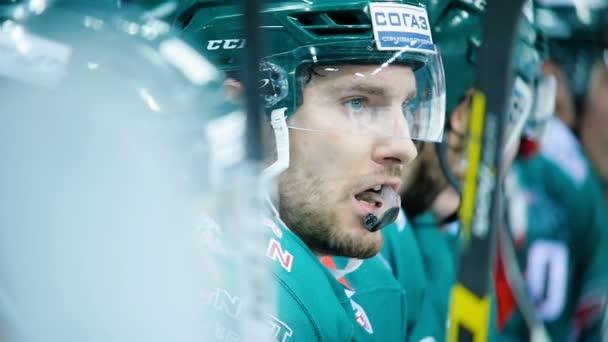 Zpomalený pohyb hokejista v helmě sedí na lavičce s náustkem