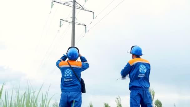 zaměstnanci v uniformě s logem společnosti sledovat vedení vysokého napětí