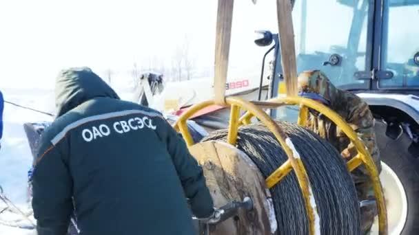 i lavoratori fissare la bobina di filo di acciaio corda vicino a trattore in inverno