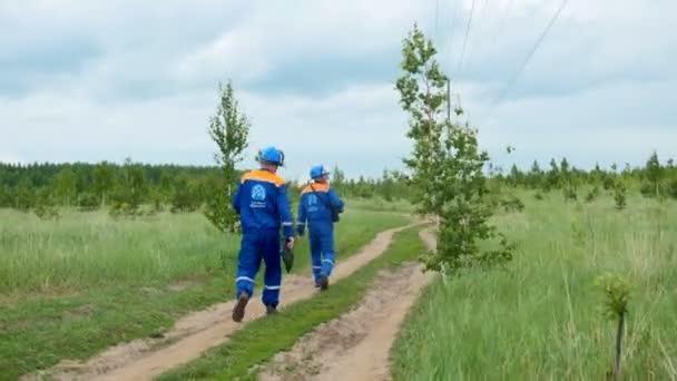 dělníci v uniformě s logem chodit po silnici pod vedení vysokého napětí