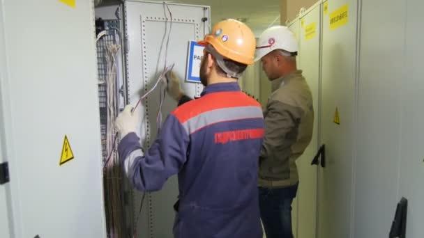 electricians in logo uniform mount equipment in switchgear case