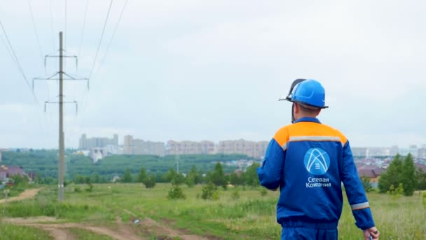 KAZAN, TATARSTAN RUSSIA - MAY 28 2018: Backside view worker in logo jacket and helmet walks along ground track to distant village with electric post on May 28 in Kazan