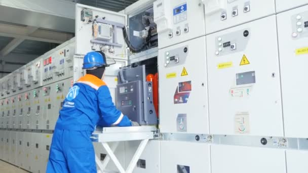 employee pulls large electrical device out of switchgear case standing in row