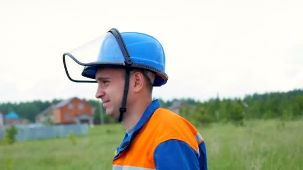 zaměstnanec v jednotných helmu s skleněný štít chodí kolem stromy a domy