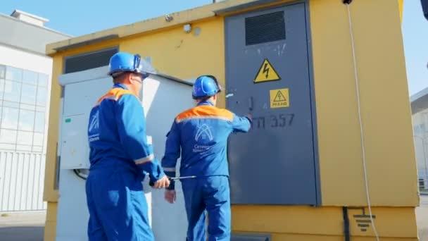engineers open door enter transformer box premises with equipment