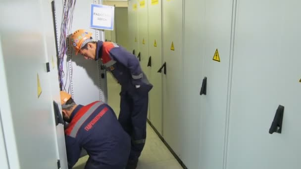 electricians with company logo check equipment in switchgear case in corridor