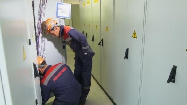 elettricisti con logo aziendale verifica attrezzature in caso di impianti di distribuzione in corridoio
