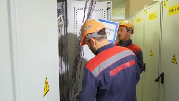 employees in form with firm logo take wires to mount inside switchgear case