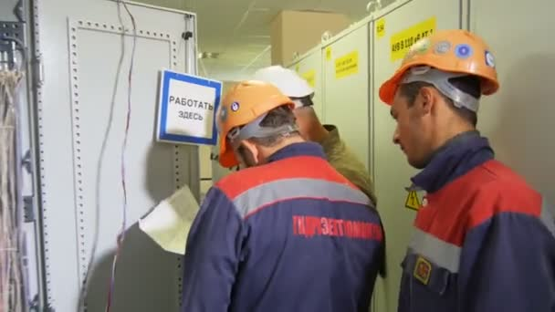 KAZAN, TATARSTAN RUSSIA - MAY 30 2018: Side view technicians in uniform with company logo and documents discuss problem near network power cabinets on May 30 in Kazan
