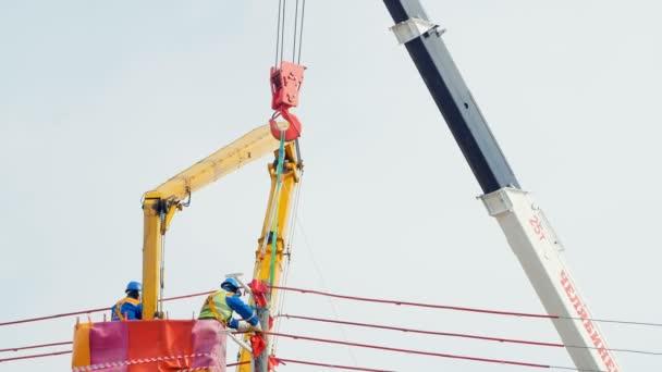 technicians in hanging crane cradle work with wires under grey sky