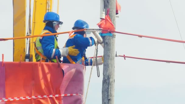 employees operate with electric cable on wooden pole in crane cradle