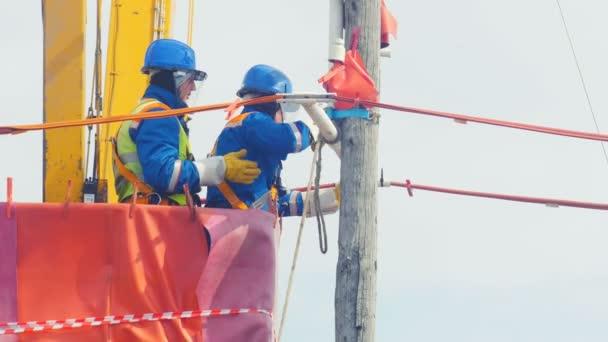 dipendenti operano con cavo elettrico sul palo di legno nella culla di gru