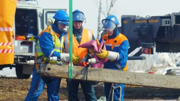 KAZAN, TATARSTAN RUSSIA - MAY 23 2018: Professional electricians in warm jackets cover installed transmission post details with rubber sheets on brown ground on May 23 in Kazan