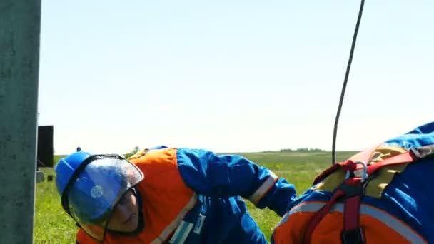 workers fix metal leg-irons among green meadow under blue sky