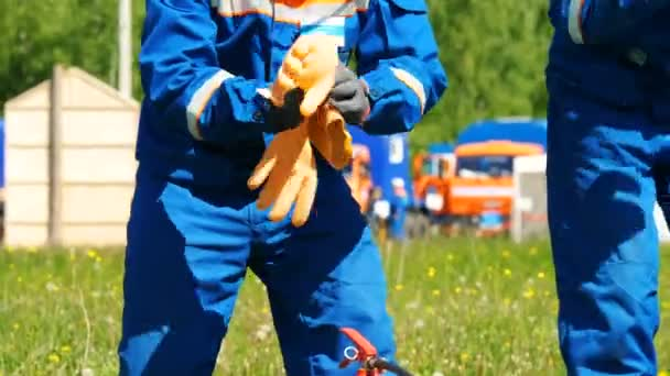 competitors put on rubber gloves and boots by fire extinguisher on field