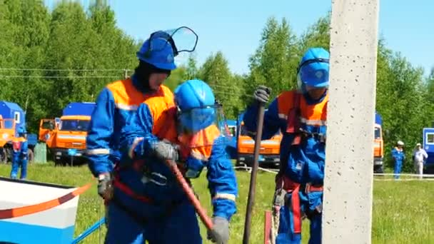 employees fix pole for transmission lines on field at competitions