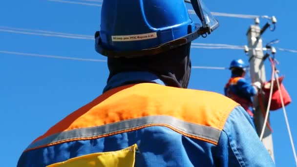electricians fix electric cable on post against blue sky