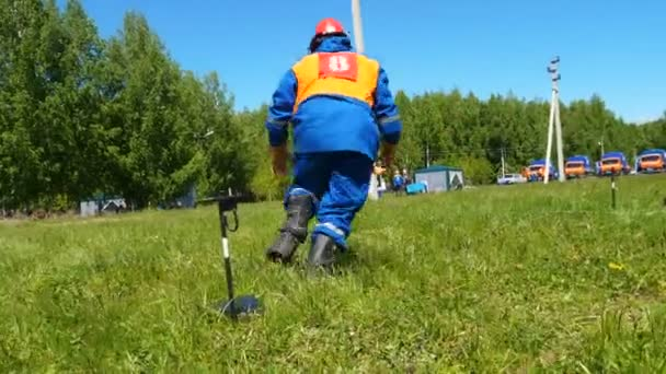 man with number on back puts on boots and throws rope over high voltage line