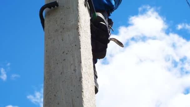 Kazan, Russia Tatarstan - 23 maggio 2018: Ragazzo di vista vicina in uniformi casco e stivali di gomma si arrampica dal palo concreto con ceppi contro la foresta ed il cielo blu alle competizioni il 23 maggio a Kazan