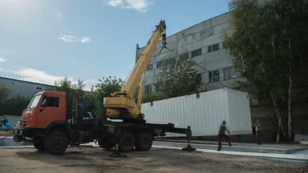 timelapse auto crane transports white container near plant