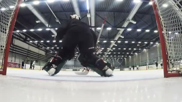 zkušený brankář v černém brání cíle na hokejový zápas