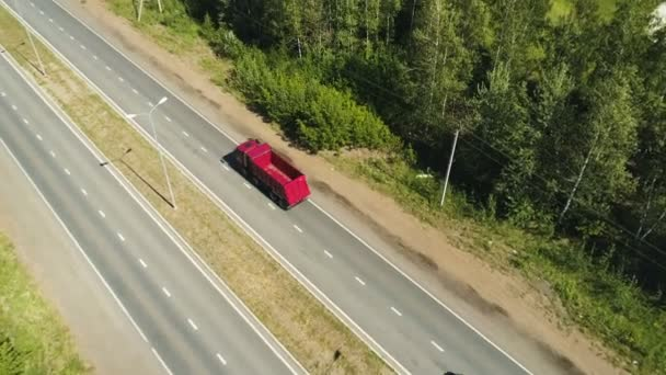 red lorry moves along highway to distant city on horizon