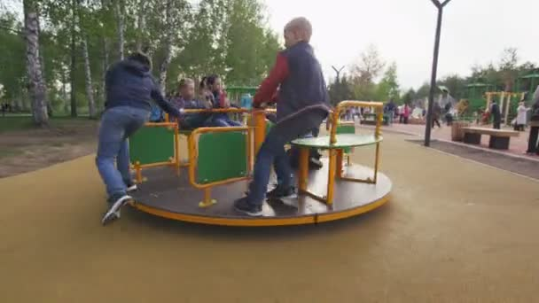 happy children rotate on bright carousel on large playground