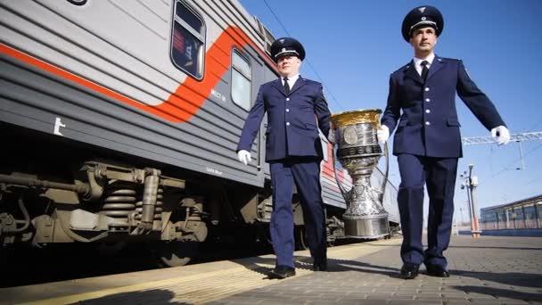 slow motion men in uniform carry winner cup along train