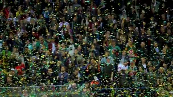slow motion confetti falls down on arena against spectators