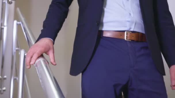 man goes down stairs with metal handrail slow motion closeup