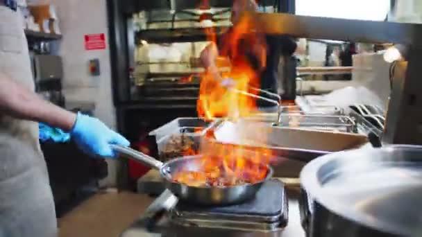 kuchař hoří v pánvi s masem na ohni