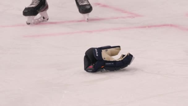 hockey player takes glove fallen on rink at sports game