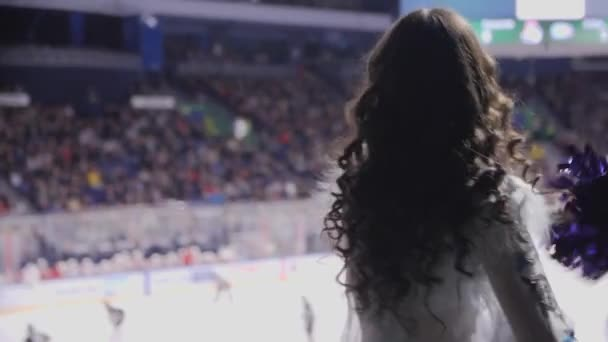 lady in sexy snow maiden dress dances with pompoms on rink