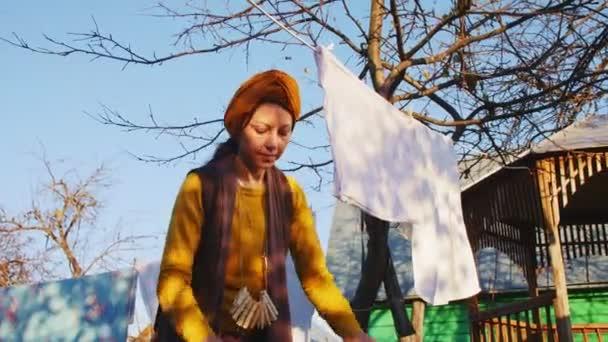 nő sárga lóg tiszta törülköző kötélen a ház udvarán