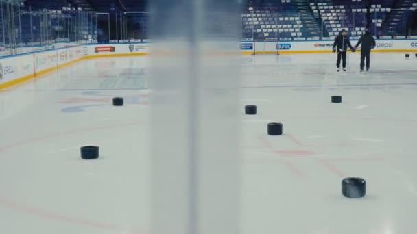 sportovci v teplákových soupravách vlak s hokejkami na aréně