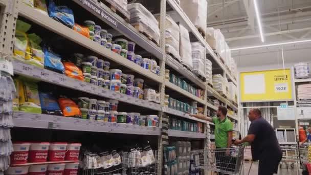 zkušený prodejce ukazuje zboží na stojanu plešatému zákazníkovi