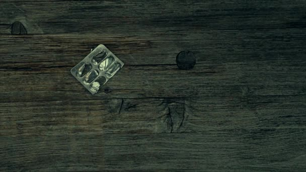 Overdose -  pills in hand addict lying on the floor