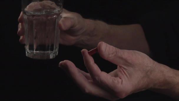 Nahaufnahme. Hand eines alten Mannes mit einer Pille auf schwarzem Hintergrund Begriff Krankheit und Gesundheitswesen