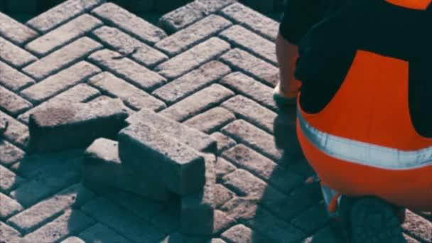 Sidewalk chodník stavební prácestavební dělník umístění kamenných dlaždic v písku pro dlažbu, terasa. Pracovník umísťující žulovou dlažbu na terasu