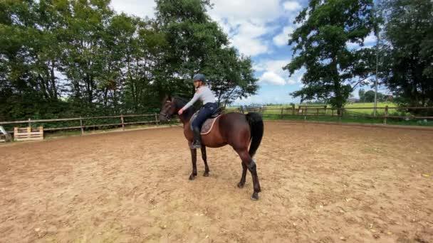 Junge Reiterin sitzt hoch zu Ross an einem sonnigen Sommertag. Kinder auf Ranch