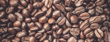 Coffee beans fresh roasted arabica robusta food background Coffea grains ready to cook most delicious and popular beverage in world of espresso cappuccino latte Top view macro vintage toned image.