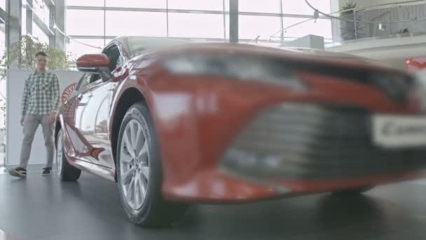 Mann läuft um neues rotes Auto herum und lächelt.
