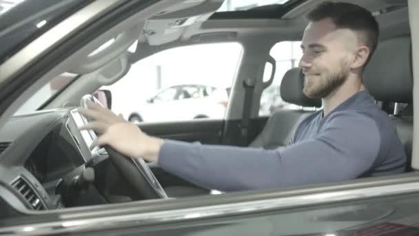 Man enjoying car interior in new automobile in auto salon
