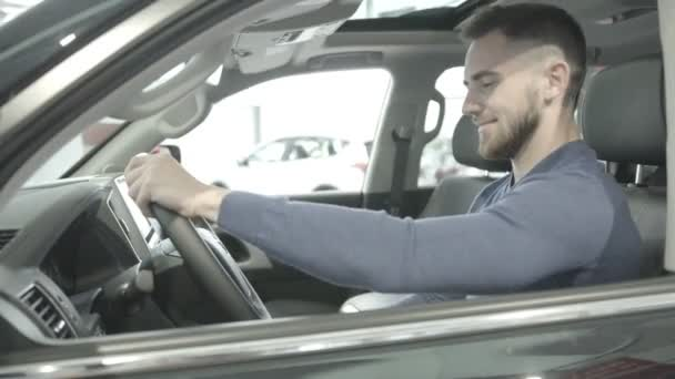 A kind of closeup of a happy man sits in a new car.