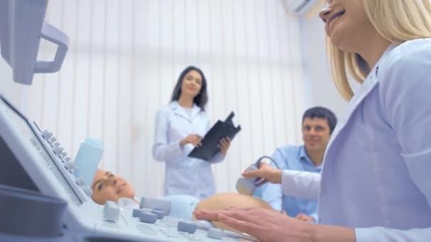 eine schwangere Frau ruht auf einer Couch in einem Schrank mit Ultraschalldiagnostik, spricht und hält Händchen mit einem glücklichen Ehemann und einer Ärztin, um Ultraschalluntersuchungen durchzuführen