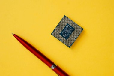 The processor for socket LGA 1151 on a yellow background next to the pen. Computer techologies.