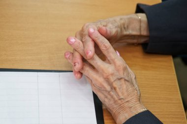 Hands of an elderly woman sitting at a table suffering from stra