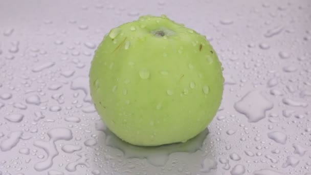 Rotation, drops of water fall on a ripe green apple.