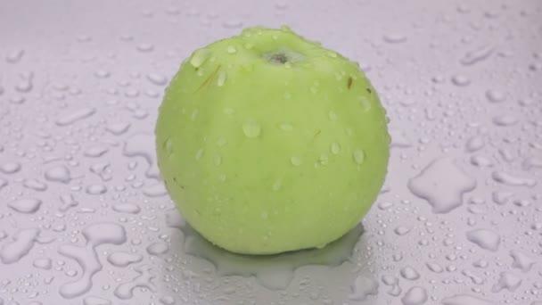 Rotace, kapky vody padají na zralé zelené jablko